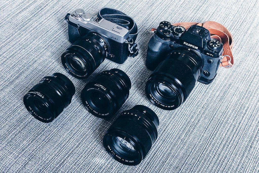 Työvälineenä toimivat kamerat Fuji X-E1 (vas.) objektiivilla 18-55mm/F2.8-4, sekä X-T1 kiikarilla 90mm/F2. Lisäksi edustalla linssit 14mm/F2.8 (vas.), 23mm/F1.4 ja 56mm/F1.2.