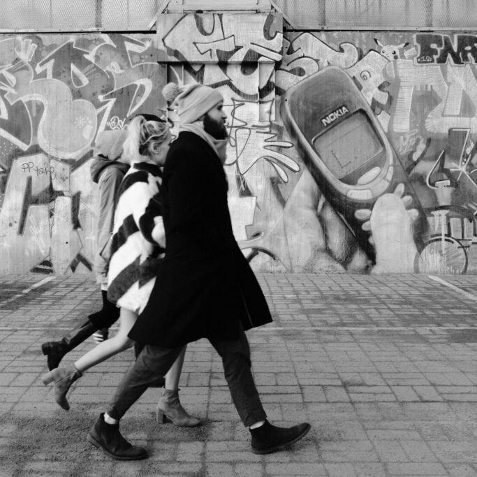 Kävelijöitä graffitin edessä