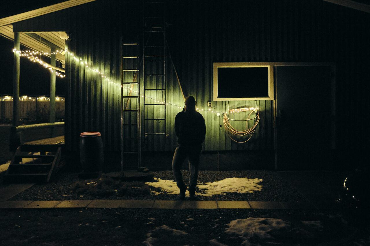 Hahmo pimeällä seinustalla
