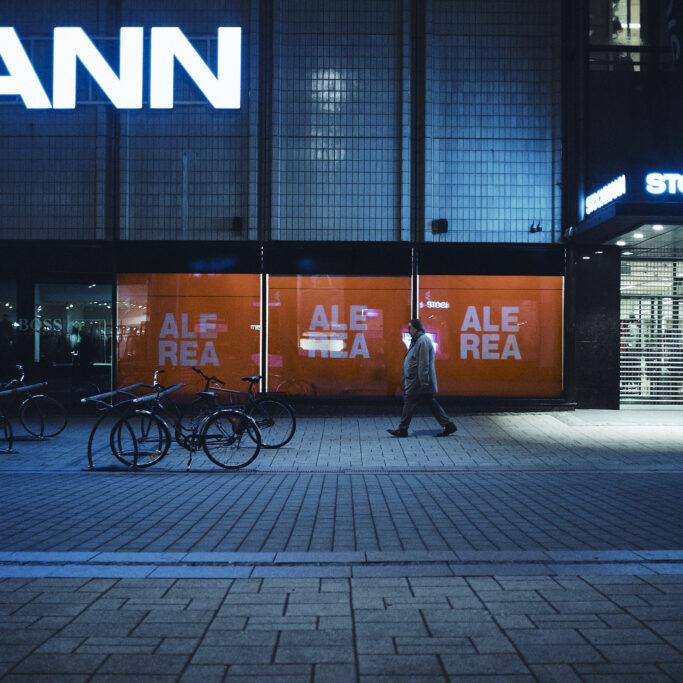 Kävelijä kauppakeskuksen edessä illalla