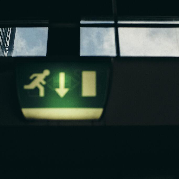 Exit-kyltti ja taivas ikkunassa