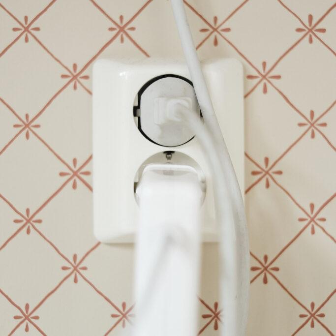 Sähköjohdot ja pistorasia tapetoidulla seinällä