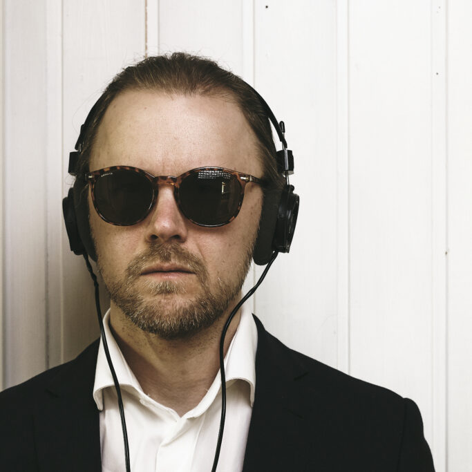 Mies aurinkolaseissa ja kuulokkeet korvilla