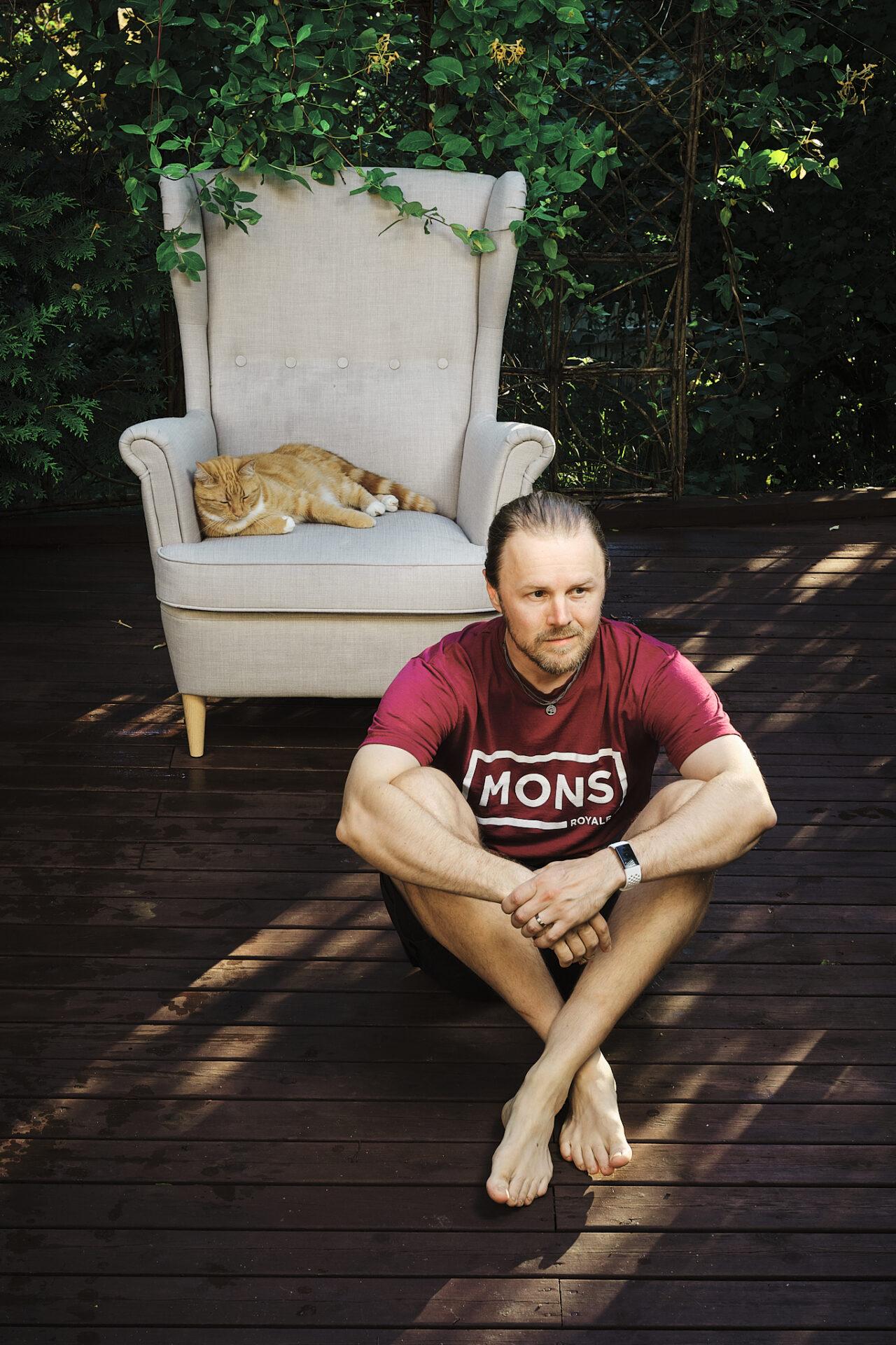 Mies lattialla ja kissa nojatuolissa terassilla
